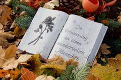 Livre de pierre avec le texte allemand sur une tombe Photographie stock libre de droits