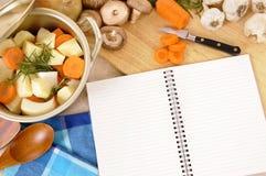 Livre de recette avec le plat de cocotte en terre et légumes organiques sur le plan de travail de cuisine, l'espace de copie Photographie stock