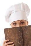 Livre de recettes de lecture de cuisinière de femme Photographie stock libre de droits
