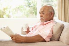 Livre de relevé d'homme aîné avec la boisson à la maison Images libres de droits