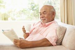 Livre de relevé d'homme aîné avec la boisson à la maison Photographie stock