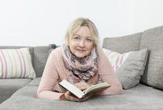 Livre de relevé de femme sur le sofa Photo stock