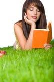 Livre de relevé de fille dans l'herbe Photo stock