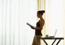 Livre de relevé de jeune femme se penchant contre la table Photo stock