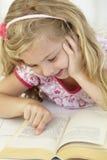 Livre de relevé de jeune fille dans la chambre à coucher Photographie stock libre de droits