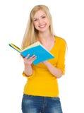 Livre de relevé de sourire de fille d'étudiant Photographie stock