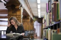 Livre de relevé de femme dans la vieille bibliothèque Photo libre de droits