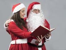 Livre de souhait de lecture d'elfe du père noël et de fille photographie stock