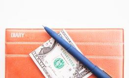 Livre, dollars et stylo sur un fond blanc Images libres de droits