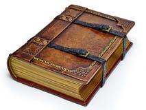 Livre en cuir âgé avec des courroies et des bords de papier dorés - s'étendant sur la table d'isolement photographie stock