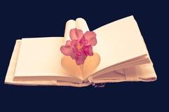 Livre en forme de coeur avec la fleur d'isolement sur le fond noir Images libres de droits