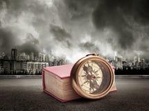 Livre et boussole sur la vue de la ville en ciel orageux images stock