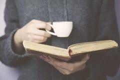 Livre et café de main de femme Photos stock