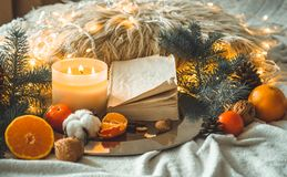 Livre et mandarines dans une composition en hiver, arbres de Noël, bougies, cônes, coton, cannelle Symbole de nouvelle année et d photo stock