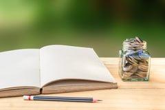 Livre et pièce de monnaie dans le pot en verre sur la table en bois avec le crayon Photo libre de droits