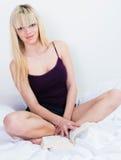 Livre et séance de relevé gai de jeune fille avec en tailleur Photos stock