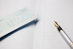 Livre et stylo de chèque Photographie stock libre de droits