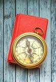 Livre fermé rouge avec la rétro boussole photo stock