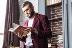 Livre intéressé de lecture de sentiment d'homme d'affaires concernant l'astrologie et l'argent images stock