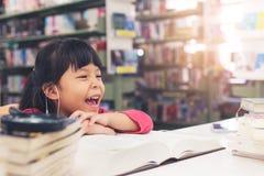 Livre lu de sourire de tissu de rose de fille d'enfants à la bibliothèque Image stock