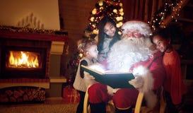 Livre magique de lecture de Santa Claus avec des enfants Photos stock