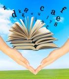 Livre magique et les lettres au-dessus des mains Photographie stock libre de droits