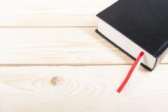 Livre noir avec le repère rouge et blanc sur la table en bois De nouveau à l'école Copiez l'espace Image stock