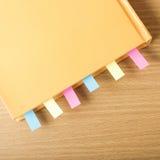 Livre orange avec la note collante photographie stock libre de droits