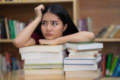 Livre ou manuel de lecture ennuyé ou contrarié de garçon d'étudiant au libr Image stock