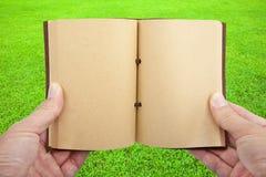 Livre ouvert à disposition sur l'herbe photographie stock