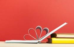 Livre ouvert avec des pages dans la forme du coeur Fond rouge L'espace d'exemplaire gratuit Photographie stock libre de droits