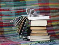 Livre ouvert avec les pages en forme de coeur sur le fond coloré Images stock