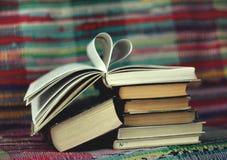 Livre ouvert avec les pages en forme de coeur sur le fond coloré Image stock