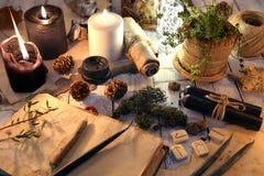 Livre ouvert, bougies noires et blanches, runes et succulent sur la table de sorcière photos stock