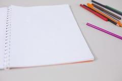 Livre ouvert de blanc vide sur le bureau d'école avec des crayons Photos libres de droits