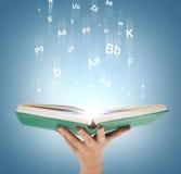 Livre ouvert de participation de main avec les lumières magiques Image libre de droits