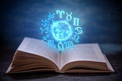 Livre ouvert sur l'astrologie sur un fond foncé Globe magique rougeoyant avec des signes du zodiaque dans la lumière bleue photos libres de droits