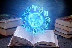 Livre ouvert sur l'astrologie sur un fond foncé Globe magique rougeoyant avec des signes du zodiaque dans la lumière bleue photo libre de droits