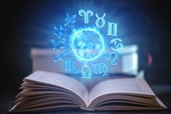 Livre ouvert sur l'astrologie sur un fond foncé Globe magique rougeoyant avec des signes du zodiaque dans la lumière bleue image libre de droits