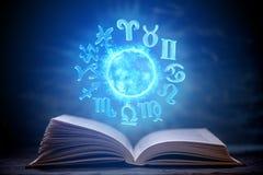 Livre ouvert sur l'astrologie sur un fond foncé Globe magique rougeoyant avec des signes du zodiaque dans la lumière bleue images libres de droits