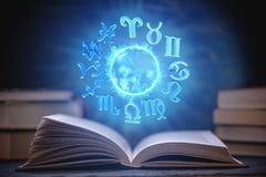 Livre ouvert sur l'astrologie sur un fond foncé Le globe magique rougeoyant avec des signes du zodiaque dans la lumière bleue photographie stock libre de droits