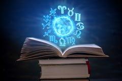 Livre ouvert sur l'astrologie sur un fond foncé Le globe magique rougeoyant avec des signes du zodiaque dans la lumière bleue photo stock