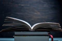Livre ouvert sur une pile de livres sur une table sur un fond foncé Préparation d'examen dans les écoles et les universités photo stock