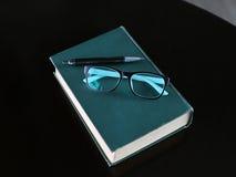 Livre relié avec le stylo et verres sur la table en bois Photographie stock