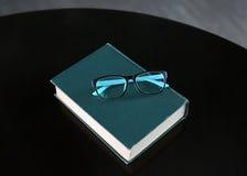Livre relié avec le stylo et verres sur la table en bois Photo stock