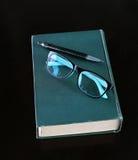 Livre relié avec le stylo et verres sur la table en bois Image stock