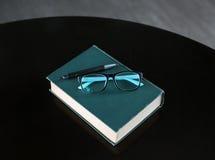 Livre relié avec le stylo et verres sur la table en bois Photos libres de droits