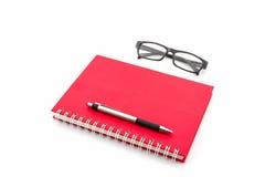 Livre rouge de journal intime avec de vieux verres et stylo Images stock