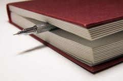 Livre rouge et crayon mécanique en dedans images stock