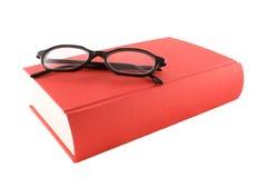 Livre rouge et glasses1 noir Photographie stock